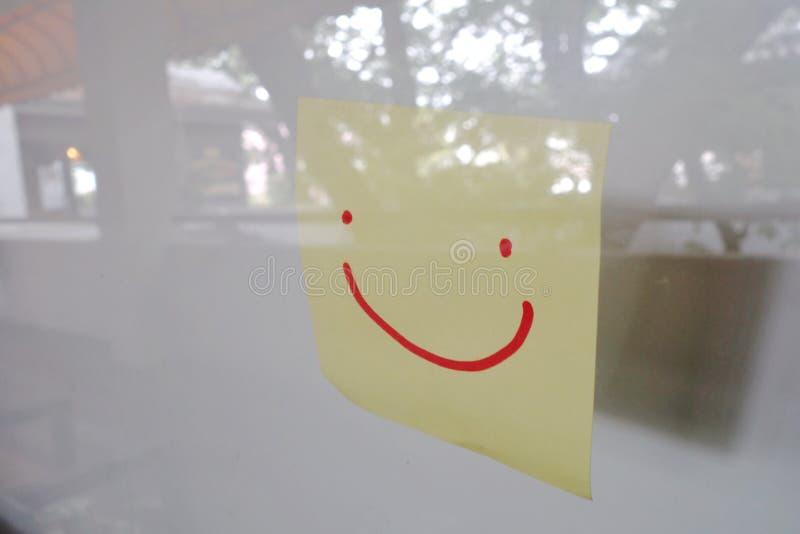 Übergeben Sie gezogenes smileygesicht auf klebriger Anmerkung über Glaswand stockfoto