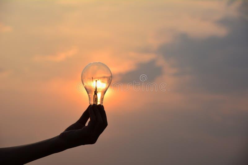 übergeben Sie Glühlampeideenkonzept und Schattenbildart darunter halten lizenzfreies stockbild