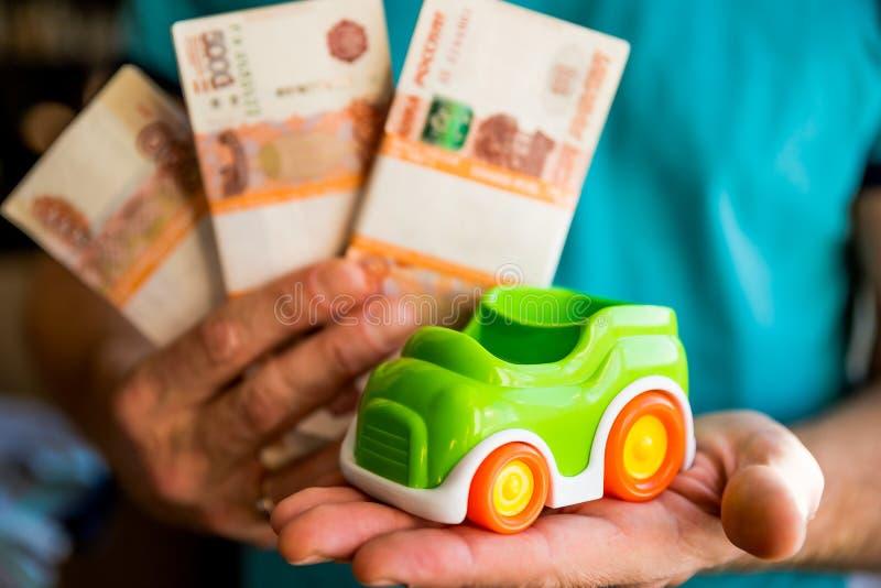 Übergeben Sie Griff grünes Spielzeugauto und russisches Geld feste Rate für Autokredit oder Einsparungsgeld für Auto, Geschäftsau lizenzfreies stockfoto