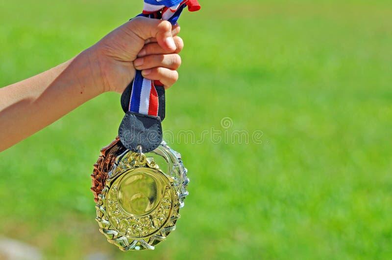 Übergeben Sie Griffgold-, silberne und Bronzemedaille mit grünem Feld backgro lizenzfreie stockfotografie