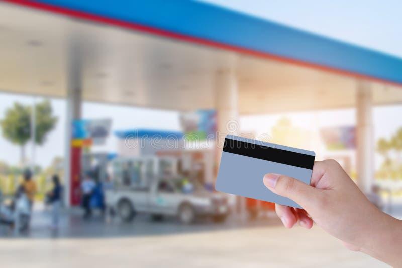 Übergeben Sie Griffkreditkartezahlung mit Tankstellehintergrund stockfotografie