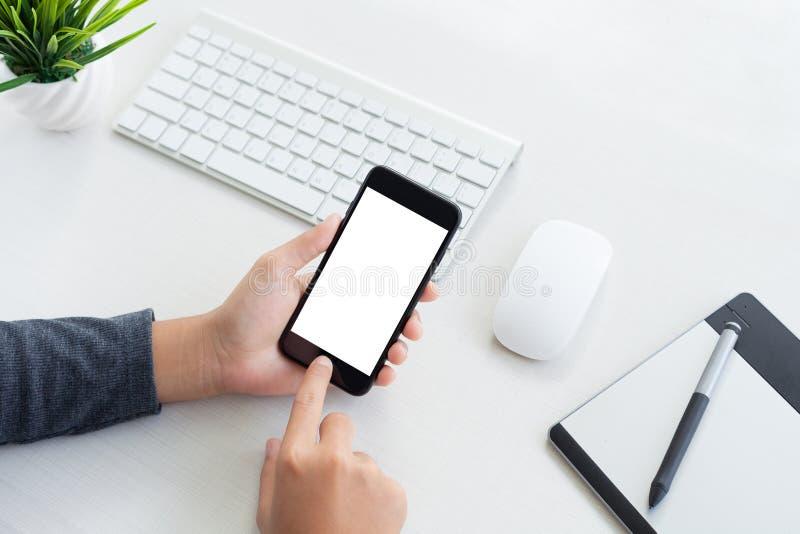 Übergeben Sie Grifftelefon und das Berühren auf Arbeitsplatztabelle stockfotos