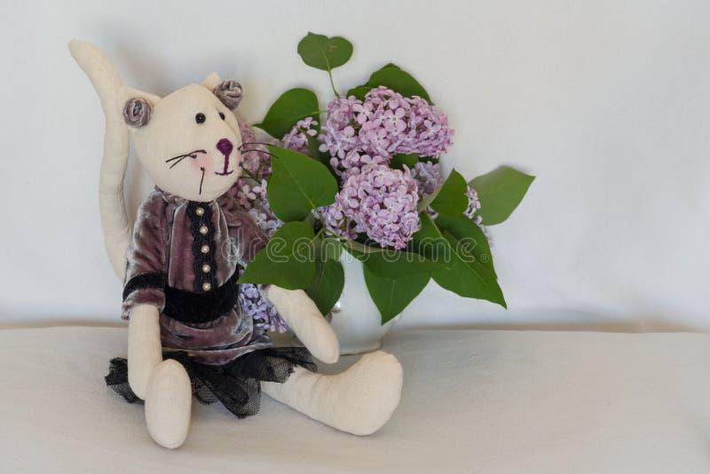 Übergeben Sie Mädchenkatze und einen Blumenstrauß der Flieder Sitzt auf einem hellen Hintergrund, Kopienraum stockfoto