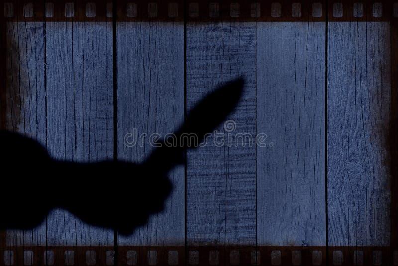 Übergeben Sie Schattenbild mit Messer auf der natürlichen Holzverkleidung lizenzfreies stockfoto