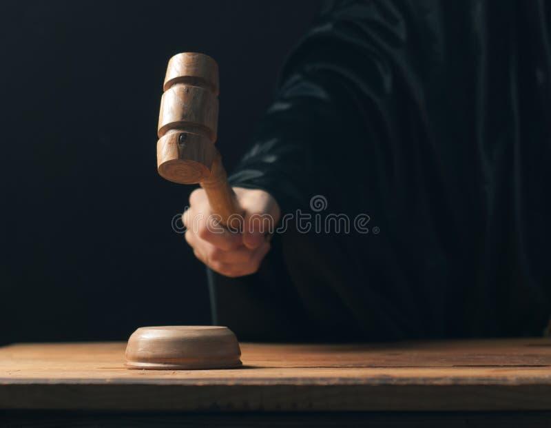 Übergeben Sie schlagenden Hammer auf dunklem Hintergrund, der Richter macht einen Urteilsspruch, stockfoto