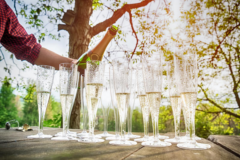 Übergeben Sie strömenden Wein in Flötengläser Champagner lizenzfreie stockfotografie