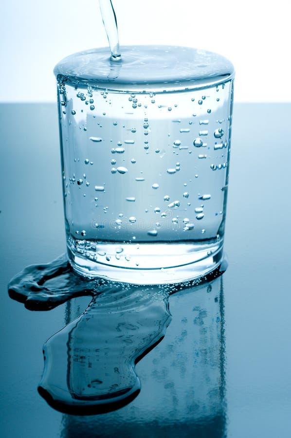 Übergelaufenes Glas Wasser lizenzfreie stockfotografie