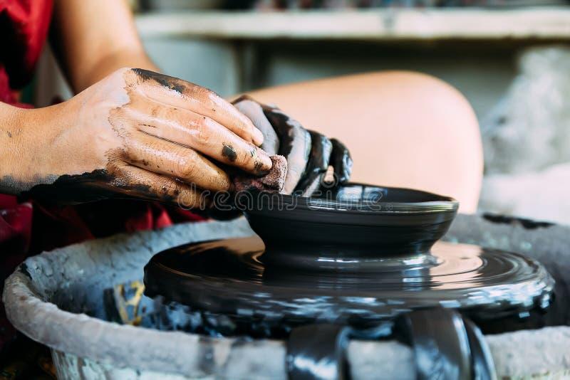 Übergibt die Nahaufnahme und arbeitet an Töpferscheibe mit Keramik stockfotos