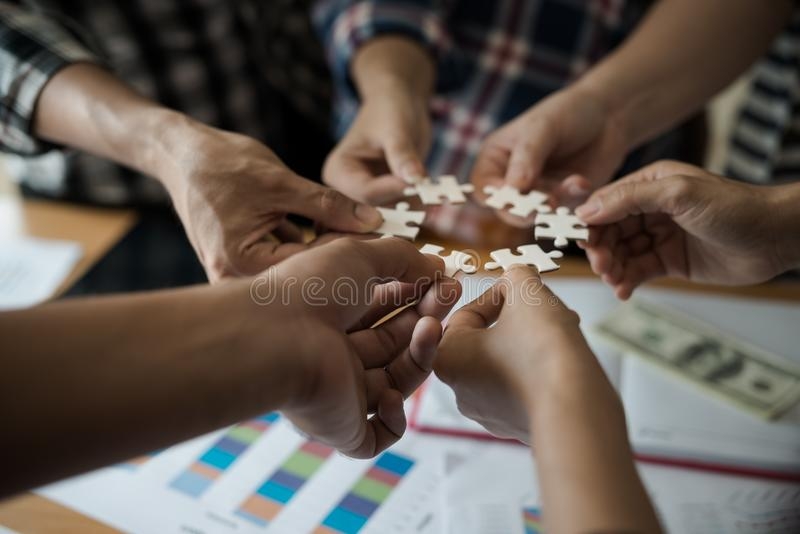 Übergibt Gruppe Geschäftsleute, die Puzzleweiß zusammenbauen B stockbild
