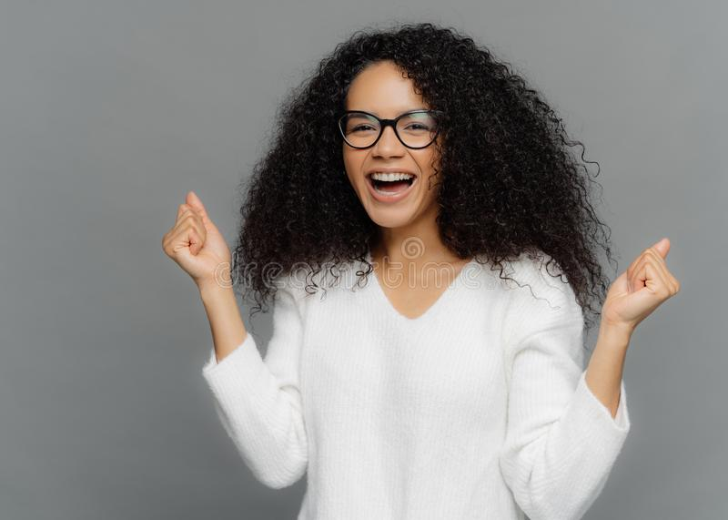 Überglückliche Afroamerikanerfrau preßt Fäuste mit Triumph, Lachen mit Glück, sich freut Erfolg, trägt die Schauspiele zusammen,  lizenzfreies stockfoto