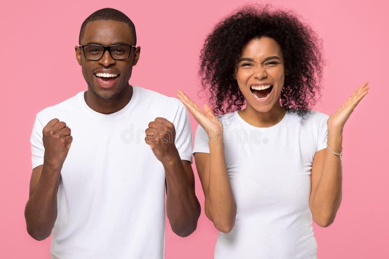 Überglückliche aufgeregte Afroamerikanerfamilien-Paarsieger feiern Sieg stockfotos