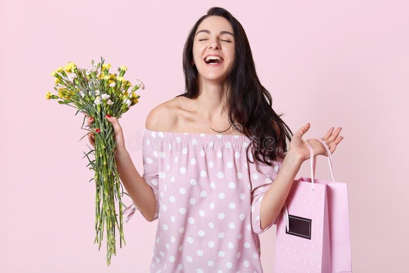 Überglückliche Frau empfängt wünschenswertes Geschenk, hält die Tasche und Blumen, Lachen glücklich, gekleidet im rosa purpurrote lizenzfreie stockbilder