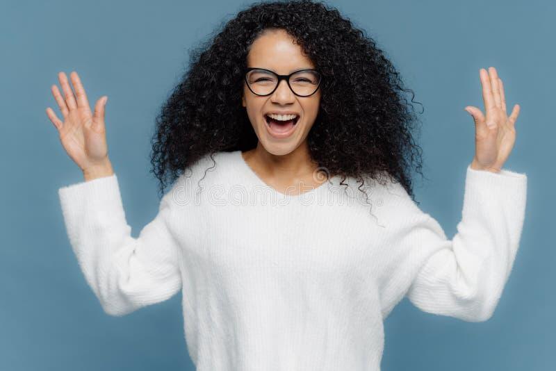 Überglückliche Mischrassefrau mit dem gelockten Haar, hebt Hände, ausruft von den positiven Gefühlen an, hält Mund geöffnet, ange lizenzfreies stockbild