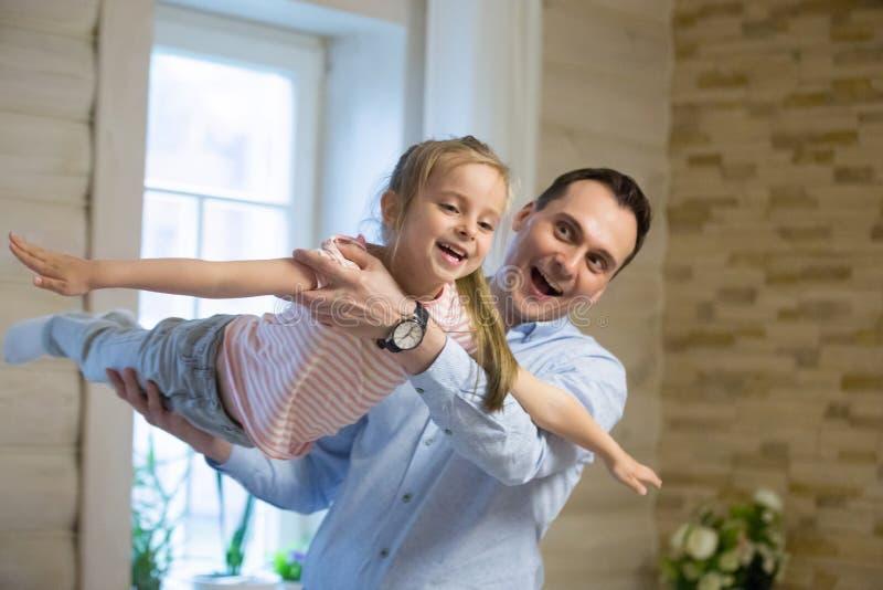 Überglücklicher Vater und Tochter, die zu Hause am Wochenende spielt lizenzfreie stockbilder