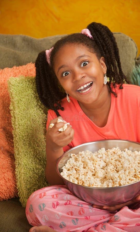 Überglückliches kleines Mädchen mit Popcorn stockfotos