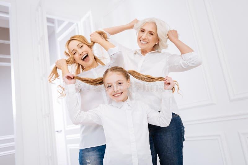 Überglückliches Mädchen und ihre Mutter mit dem Großmutterstillstehen lizenzfreie stockfotografie