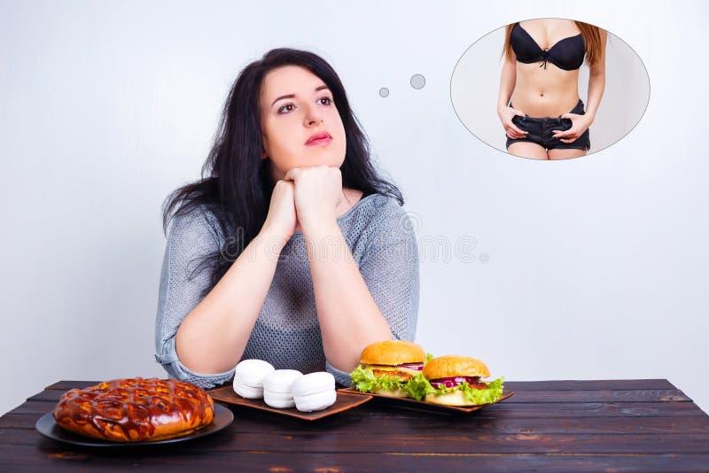 Überladene beleibte Frau mit ungesunder Fertigkost träumend vom Sitz und von dünnem b lizenzfreie stockfotografie