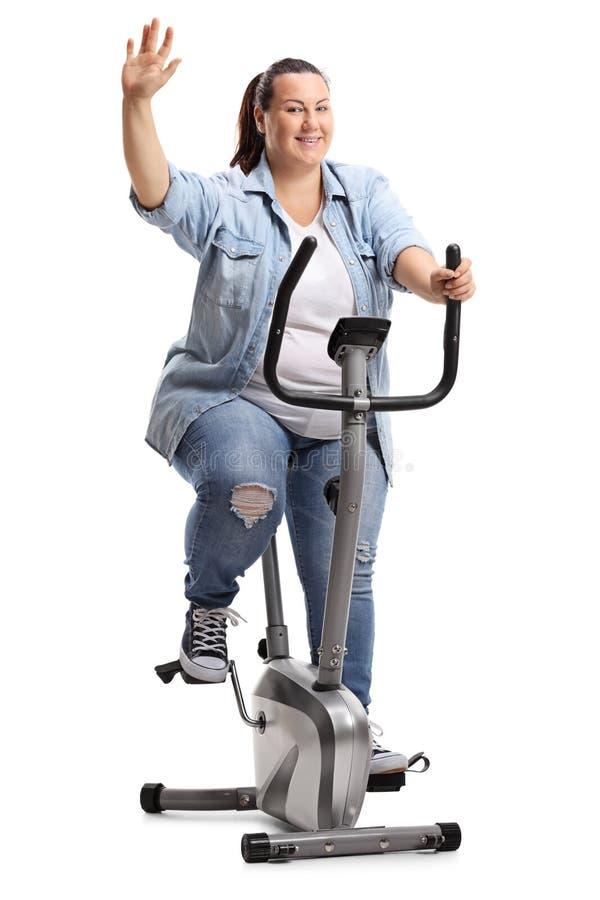 Überladene Frau, die auf einem Standrad mit den Daumen oben trainiert lizenzfreies stockfoto