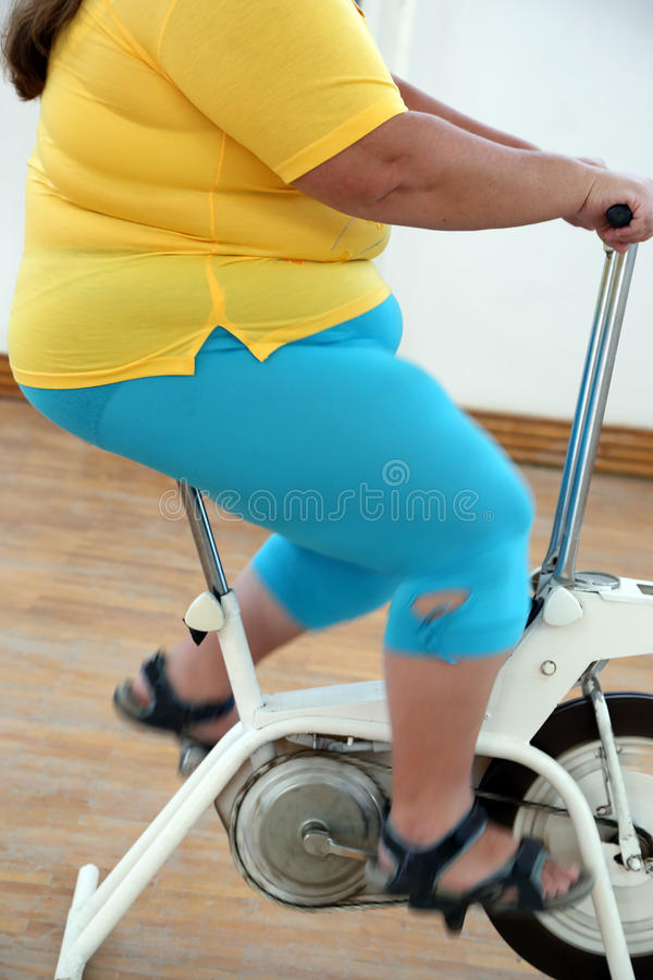 Überladene Frau, die auf Fahrradsimulator trainiert stockbild