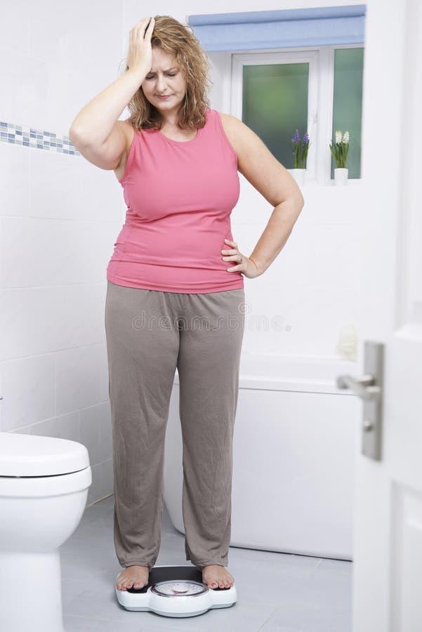 Überladene Frau, die auf Skalen im Badezimmer sich wiegt stockfotos