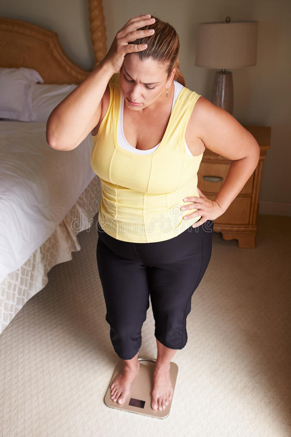 Überladene Frau, die auf Skalen im Schlafzimmer sich wiegt stockfoto
