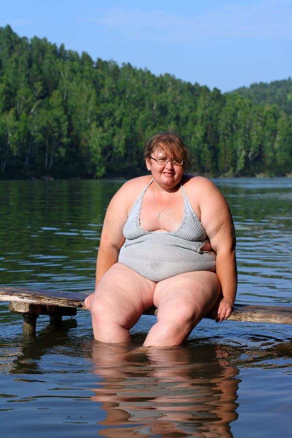 Überladene Frau, die auf Stufe sitzt lizenzfreie stockfotografie