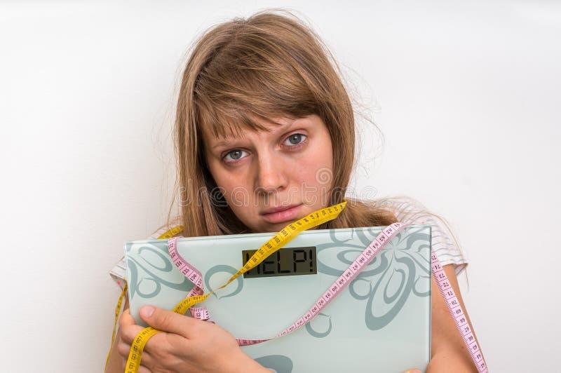 Überladene Frau, die digitale Skalen mit Wort HILFE hält! lizenzfreie stockfotografie
