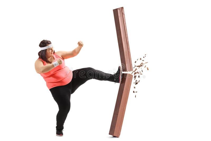 Überladene Frau, die einen Schokoriegel tritt stockfotografie