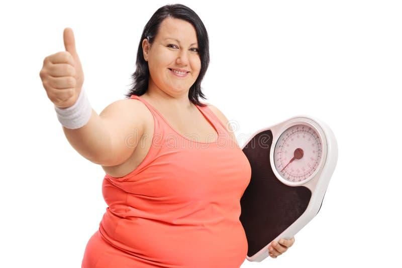 Überladene Frau mit der Gewichtsskala, die Daumen herauf Zeichen herstellt lizenzfreie stockfotos