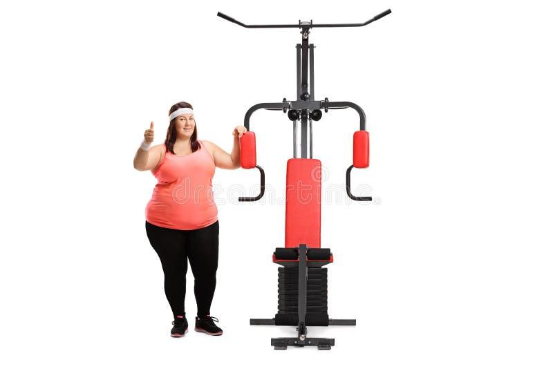 Überladene Frau mit einer trainierenden Maschine, die Daumen ist zeigt oben stockfotos