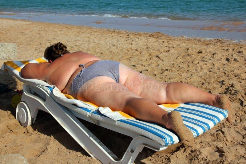 Überladene Frau nehmen auf Strand ein Sonnenbad lizenzfreie stockbilder