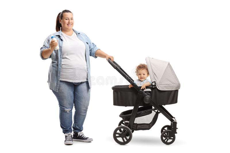 Überladene Mutter, die Babyflasche mit einem Spaziergänger O hält lizenzfreie stockfotos