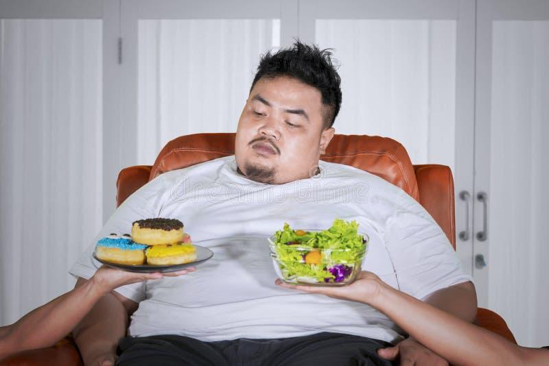 Überladener Mann, der beschließt, Schaumgummiringe zu Hause zu essen stockbild