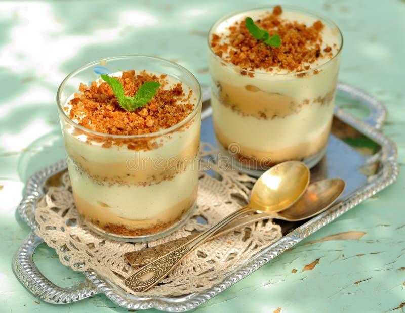Überlagerter Nachtisch in den Gläsern, in zerfallenem Keks, in der Karamellsoße, im Vanillevanillepudding und in den Bananen stockbild