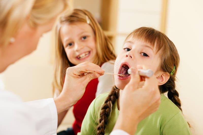 Überprüfenkehle des Kinderarztdoktors des Mädchens lizenzfreie stockbilder
