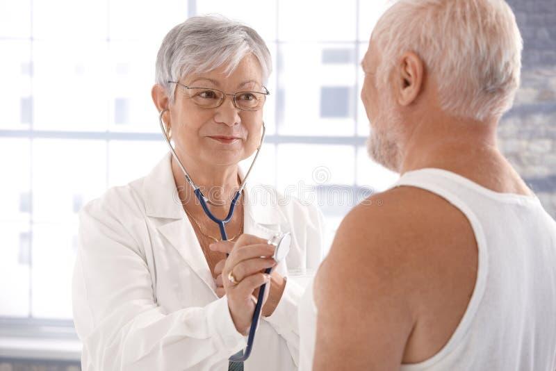 Überprüfenpatient des älteren weiblichen Doktors lizenzfreies stockbild
