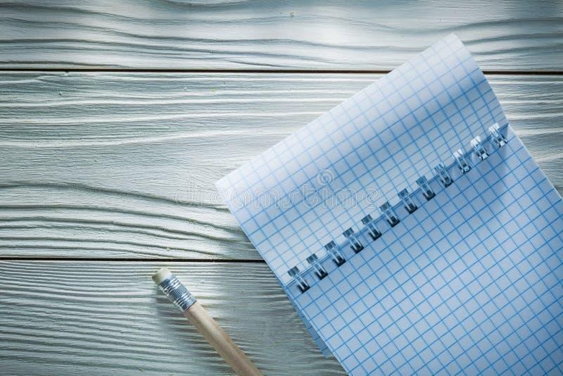 Überprüfter Bleistift des gewundenen Notizbuches auf weißem hölzernem Brett stockfotos