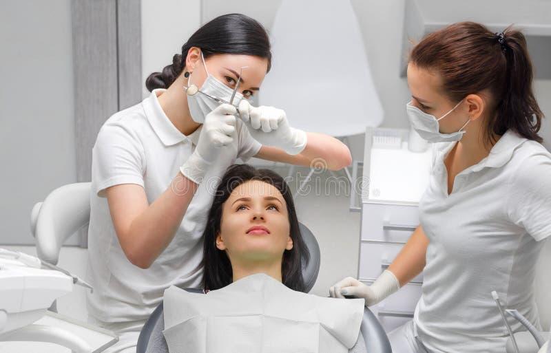 Überprüfung des Zahnarztes und des Zahnarzthelfers lizenzfreie stockbilder
