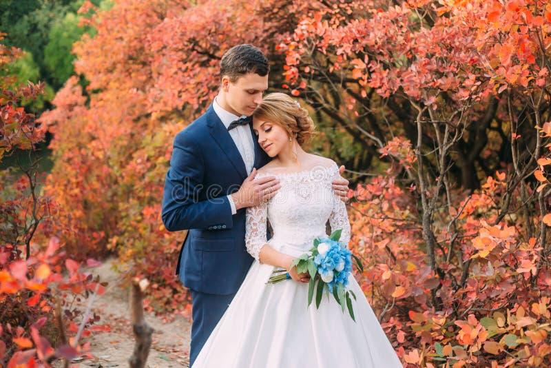 Überraschende attraktive junge Paare im Hochzeitstag Braut im eleganten weißen langen Kleid und im blauen Blumenstrauß in der Han lizenzfreie stockfotografie