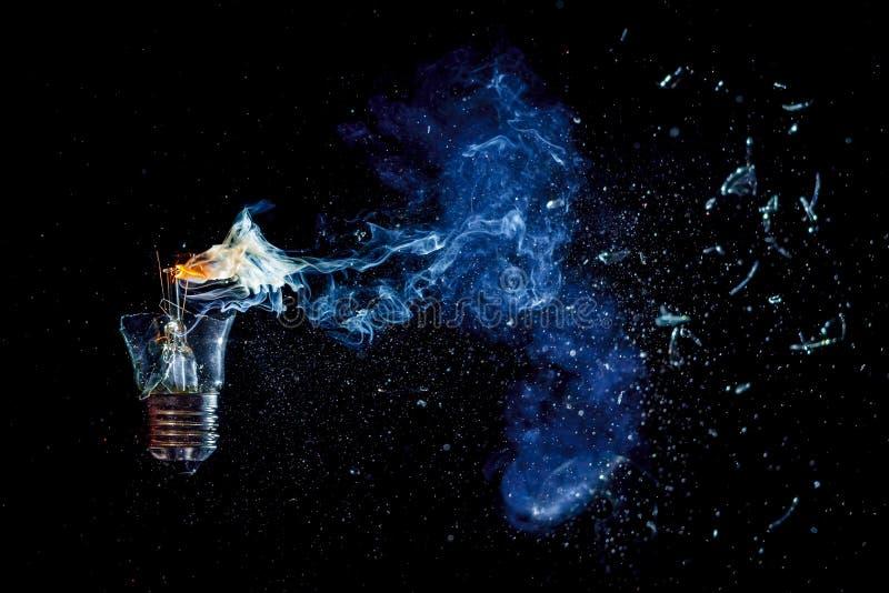 Überraschende Explosion einer brennenden Glühlampe mit Splittern und Rauche lizenzfreie stockfotos