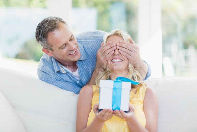 Überraschende Frau des Ehemanns mit einem Geschenk stockfoto