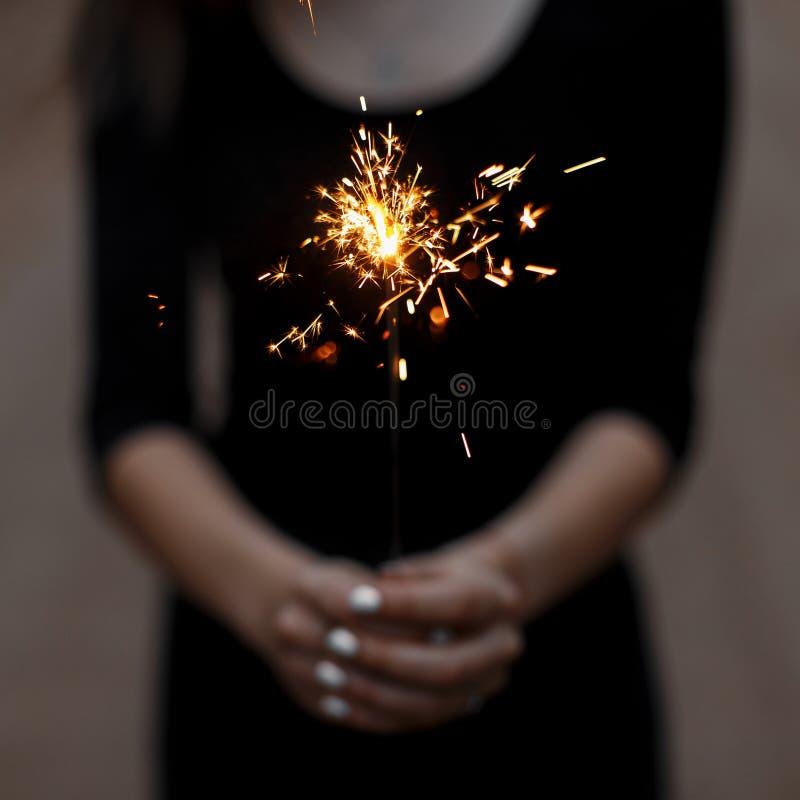 Überraschende helle festliche Wunderkerze in den Händen einer Frau Magischer Feiertagsmoment Nahaufnahme stockbilder