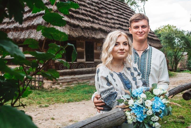 Überraschende Hochzeitspaare in einem embroidereds Hemd mit einem Blumenstrauß auf dem Hintergrund eines Holzhauses stockbild