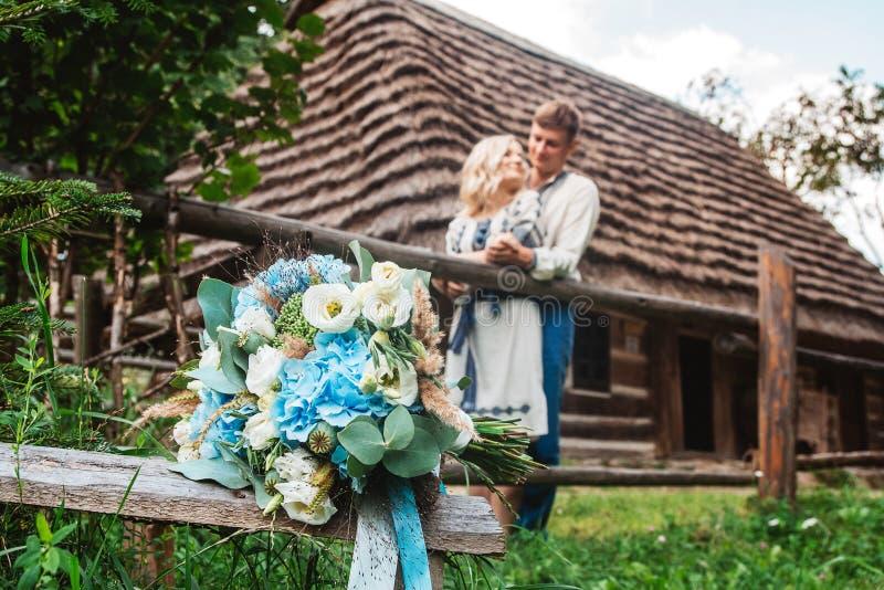 Überraschende Hochzeitspaare in einem embroidereds Hemd mit einem Blumenstrauß auf dem Hintergrund eines Holzhauses stockfotos