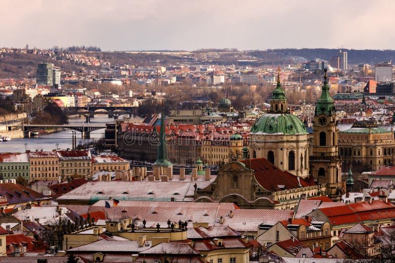 Überraschende Kirche St. Nicolas während des Wintertages nach starken Schneefällen stürmen mit Schneedecke an den Dächern Prag, T lizenzfreie stockfotos