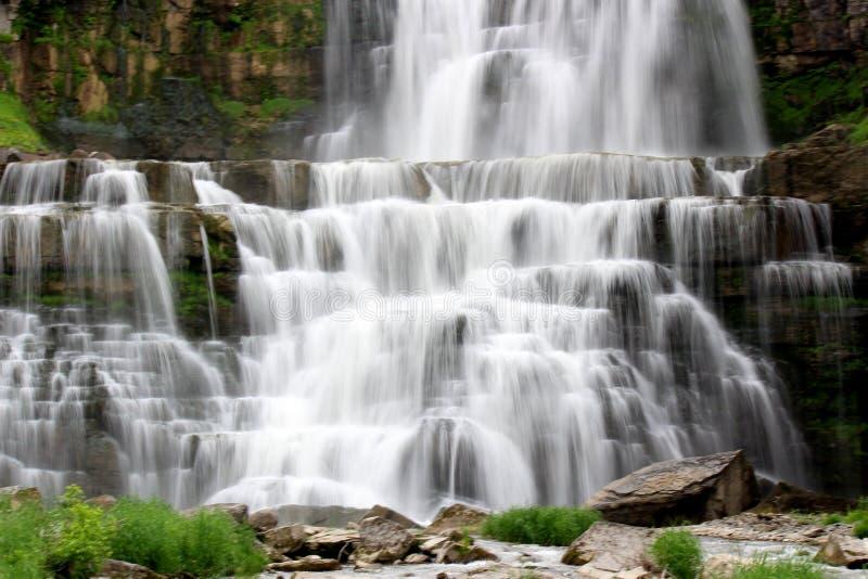 Überraschende Szene mit den Wasserfällen, die über Niveaus des alten Steins und des Sediments zum Becken unten kaskadieren lizenzfreies stockbild