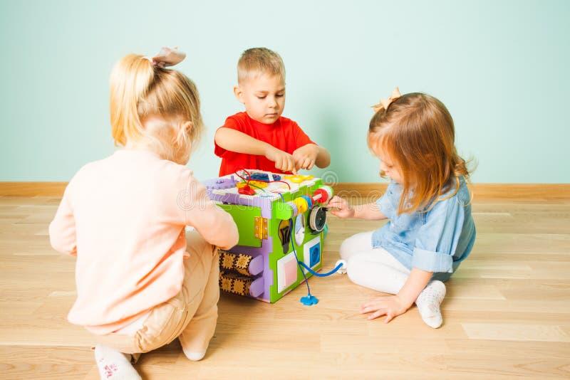 Überraschender beschäftigter Würfel und drei Kinder, die mit ihm spielen lizenzfreie stockfotografie