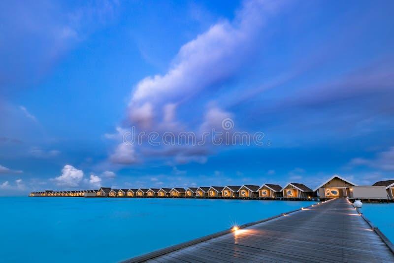 Überraschender Sonnenuntergang bei Malediven Luxus-Resort-Landhausmeerblick mit weichen geführten Lichtern unter buntem Himmel Sc lizenzfreie stockfotos