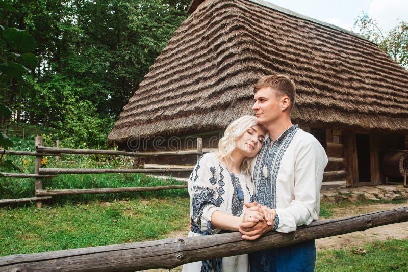 Überraschendes Heiratspaarhändchenhalten und Umarmen gegen einen Hintergrund eines Holzhauses stockbilder