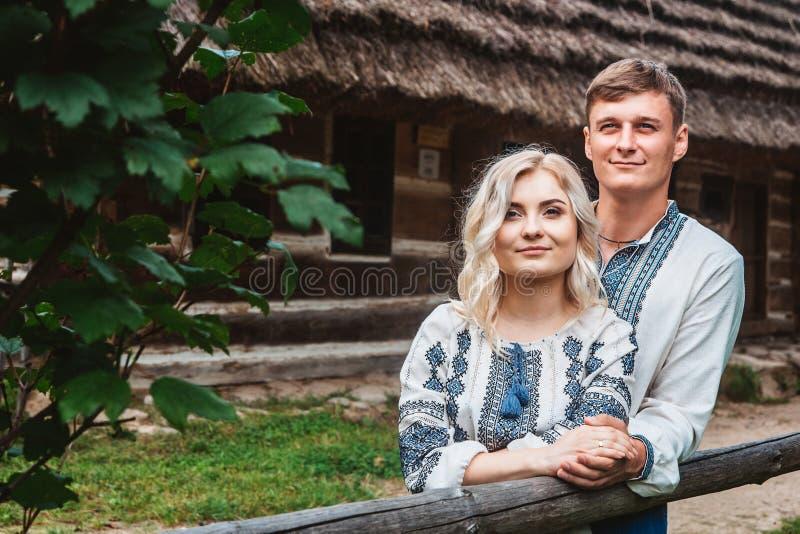 Überraschendes Heiratspaarhändchenhalten und Umarmen gegen einen Hintergrund eines Holzhauses lizenzfreie stockfotos
